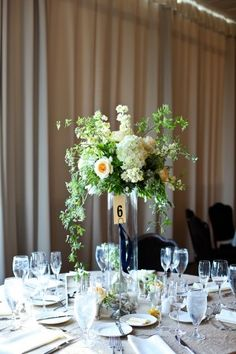 Tall centerpiece with white hydrangea, larkspur, roses, and ivy. -->good accent color with navy