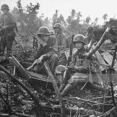 American Marines of the 1st Provisional Brigade sit in pouring rain while one of them uses a radio for communication during a lull in the fighting for the Orote Pennisula.