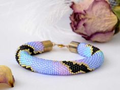 """Beaded Purple, Black, Gold, Pink, Blue Summer Seed Bead Bracelet is a perfect jewelry for bright and happy summer days. You feel yourself young and happy, you are ready to follow the wind, fly in the blue sky, dive deep in the sea, and receive all summer gifts with open heart? If ever you say """"yes, this is me"""", you absolutely need to have this bracelet softly wrap your wrist. Let it be with you every day, accumulate warmth of the sun rays, transparency and freshness of sparing rains, blue…"""