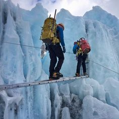 Khumbu Icefall Dangers - Photo of two Sherpa carry a heavy load across a tiny ladder