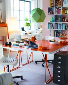 Stúdiólakás két, szembe állított narancssárga asztallal