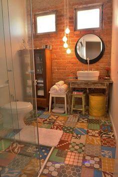 Banheiro com parede de tijolinhose piso de ladrilho hidráulico