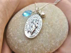 St Christopher 3-part necklace, with Aquamarine birthstone for March. St Christopher is traditionally the saint of travellers, attributed to a time when he bore Jesus Christ on his shoulders and carried him safely across a river. He has thus been entrusted to protect all travellers.