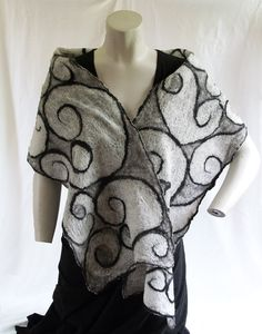 This lightweight scarf is handmade from superfine merino wool and china silk, making it soft against the skin. The scarf measures 71 long by 12 wide (180 cm x 31 cm), big enough to wrap around your shoulders on a chilly summer evening. Black and grey wool form swirls on the front; while, on the back, the sheerest layer of superfine white merino creates a wonderful crinkly texture. This scarf is great for warmer weather and can be dressed up or down.    Felting is a time- and labor-intensive…