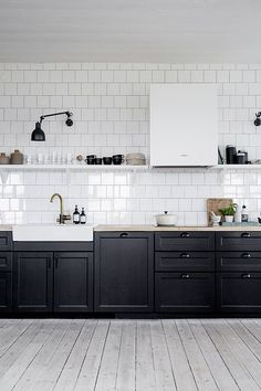 black lower cabinets, white farmhouse sink, gray concrete countertops, white backsplash, and white upper cabinets