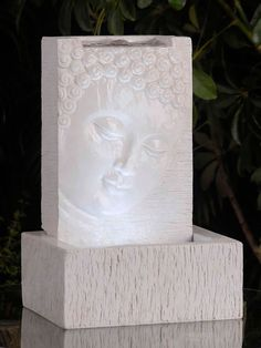 A beautiful Buddha face is featured on the front of the Tabletop Buddha Fountain With Led Light. Water flows out of the top of the fountain and over the face just before falling into the basin below.