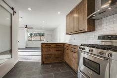 """""""After"""" photos of 10th flip - It's Great to Be Home.  Kitchen with stained maple cabinets, subway tile with gray grout, carrera marble counter, cedar + moss sconces, gray porcelain tile floor, sliding barn door, black hardware, rustic modern"""