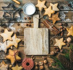 #Christmas New Year background  Christmas New Year background. Gingerbread cookies sugar powder nuts spices baking molds fir-tree branch pine cones on rustic background serving wooden board in center top view copy space