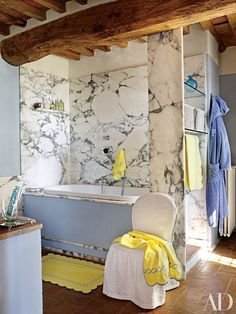 In her rustic Tuscan bathroom paved with cotto tile, decorator Dede Pratesi installed a Carrara marble bath alcove. The linens are in Pratesi's classic chain pattern.