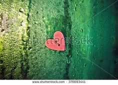 The wooden button in the shape of a heart on the window with drops of water, the button on the background of a wet window, sewing button scrap booking heart love on a window background, green light