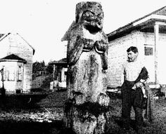 A standing bear memorial pole carved in more realistic style than on previous poles at Masset. Here the pole is shown after the top portion of the pole was cut off, just above the head of the bear. Standing next to the pole is Benjamin Bennett (son of Luke Bennett who raised this pole) - the last pole in Masset.