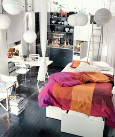 White studio apartment with bedding pops of color.