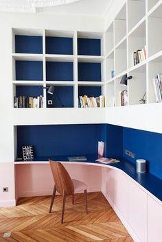 Coin bureau dans petit salon- Appartement Parisien de 320m2- GCG Architectes. Dans ce coin bureau, chaque centimètre carré est optimisé. On apprécie le fond bleu au-dessus du plateau de travail et au fond des casiers de chaque étagère.