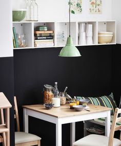 Small dining table and chairs with a wall-hung IKEA storage unit and a pendant light.
