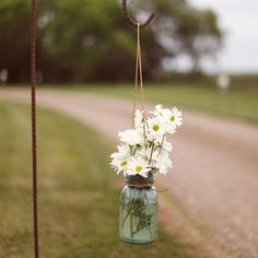 create the hooks for the glass jars they filled with water and flowers and line the road to the reception.