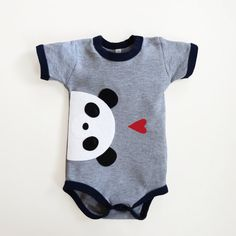 A light gray bodysuit with nautical navy binding that is made from soft and stretchy 100% cotton.  The baby panda and love heart have been hand cut