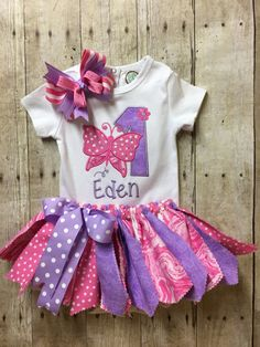 Adorable first birthday outfit includes bodysuit, tutu and boutique hair bow. Birthday bodysuit with large number one and butterfly applique. Bodysuit is white. The picture shown is an example and the fabrics may no longer be available. The colors of the fabrics and thread may be customized to your color choice. Please message me with your special request. No additional charge for change. If you do not specify, you will receive in colors shown of pink and purple. Care instructions: Machine…