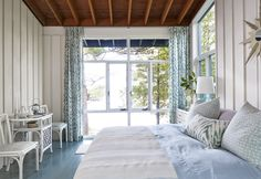 "Sarah Richardson says: ""The full-height windows make the lake feel as if it's lapping right at the floor, so I bathed the entire room in watercolor hues. Pillows and drapes offer a simple way to add softness. When updating interiors, I like to keep some elements that are a touchstone of the past. This ceiling was left natural for a warm feel, while the walls were painted pale gray."""