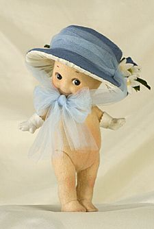 """R John Wright Dolls - Blue Bonnet Kewpie®  6"""", all felt, fully jointed, hand painted features, applied felt gloves. Wearing removeable felt, silk, and tulle bonnet. Date of Release: 2002 Ltd. Ed. 250. Part of the KEWPIE® EASTER COLLECTION."""
