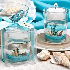 """Beach Themed Candle Wedding Favor features a clear glass outer holder with a floating seascape design, topped with a central clear plastic holder. The underwater scene includes a variety of shells, a starfish, and a sea shrub resting in a floor of vibrant blue pebbles. Sitting on top is a white wax tealight candle. It comes packaged in a clear acetate box. It is wrapped in a white satin ribbon tied into a bow on top with a calla lily design """"For You"""" gift tag."""