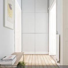 Zurückhaltender Eingangsbereich mit verstecktem Einbauschrank für Kleidung. Dieser ist in Wandfarbe gestrichen und erscheint so nicht als solitäres Möbel. Kleine Bank als Ablage und Sitzmöglichkeit zum Schuhe binden.