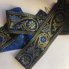 Jacquard Ribbon Trim, 5cm wide, black background with embroidered blue and gold flower design. JB001