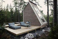 cabane en bois habitable avec terrasse, barbecue sur pieds et chaises-longues dans les forêts de Finland