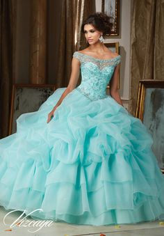 Quinceanera dresses by Vizcaya Jeweled Beading on a Billowy Organza Ball Gown Matching Bolero Jacket. Available in Light Aqua, Iced Pink White