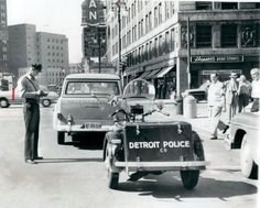 Awesome Vintage Photo... of  a Detroit Parking Cop, outside the Michigan Theatre in 1952, as he tickets a car. Maybe its owner was at a movie!