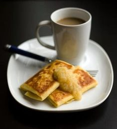 Ricotta cheese and eggs laced with vanilla and lemon are folded into a crepe to create satisfying blintzes, topped with applesauce and paired with a cup of coffee.