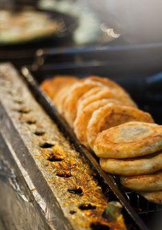 "hodduk ""fried pillow of dough surrounding a mixture of cinnamon, sugar and peanuts"""