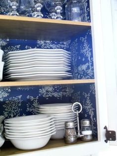 Plates Surprise Inside: Have leftover wallpaper or fabric? Covering the interior walls of a cupboard not only gives you a lovely surprise when you open the door, it highlights the china and glassware as well.