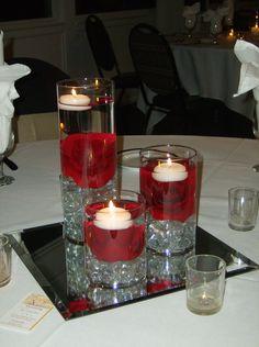 Centro de mesa con bases de vidrio tipo cilindro con rosas rojas con velas flotantes y espejo