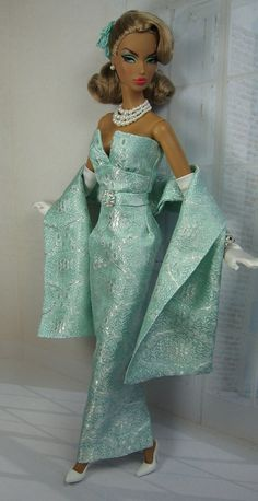 This vintage style ankle length formal sheath is cut from Tiffany blue silk brocade shot with a silver thread pattern and line in matching china silk. The gown features an attached belt with rhinestone buckle, back walking split and button over snap back closure. A long stole and floral hairpics are included. SHOES, JEWELRY, GLOVES, SUNGLASSES, PURSE, STOCKINGS, DOLL AND DIORAMA NOT INCLUDED. Accessories are from Mattel Barbie Fashion Model Collection