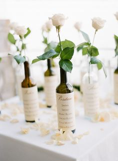 Wine bottle seating chart with a single rose. This might be cute for a vineyard or Tuscan themed wedding.