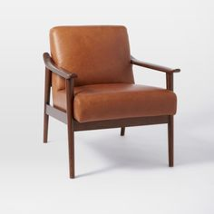 """Named for the way its aniline leather seat peeks through its solid wood frame, our Mid-Century Show Wood Chair packs good looks and comfort into one sleek silhouette. Did we mention its sculptural arms and wide, welcoming seat? 26""""w x 31.6""""d x 32.3""""h. Covered in top-grain aniline leather. Aniline leather has a natural look and soft, waxy finish that will scuff over time and develop a beautiful vintage patina with age and use. Solid wood legs with a Pecan-stained finish (Nero) ..."""