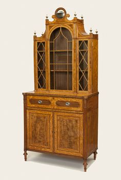 A late 18th century satinwood and faded mahogany secretaire cabinet of the finest quality and proportions, the upper section having three glazed doors, the centre door of arched form, surmounted by a circular convex mirror and eight finely turned urn finials. The lower part with a fitted secretaire drawer above cupboard doors panelled with stringing and cross-banding, flanked by reeded columns headed by acanthus leaf capitals, raised on turned and tapered feet.