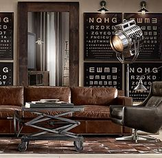 Living Room - Industrial chic - spot light floor lamps, scissor coffee table, distressed leather sofa & eye charts for your wall.....love the combo.