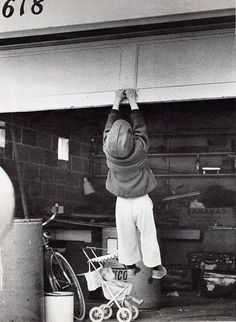 Garage doors have come a long way in 95 years. What do you think is going through this little boy's head as he gets pulled up by this garage door? ‪#OHD95 #garagedoor #blackandwhite #photography #funny