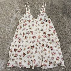 Nwt Brandy Melville Dress New! Off white colored dress with floral print along it. Has a v-neck with a line going down the middle. Has two straps on each side. No trades Brandy Melville Dresses