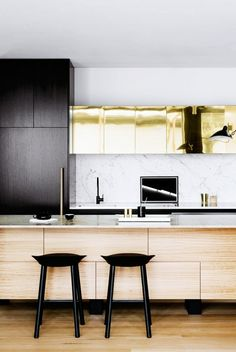 This modern kitchen gets a dose of glam with metallic gold cabinets and marble walls