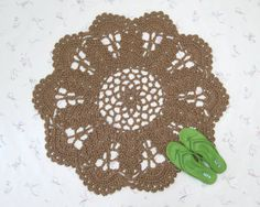 "A round jute rug, roughly flower shaped, crocheted with natural, undyed fiber. It's handmade, and measures about 36"" in diameter. The inner pattern is roughly suggestive of sheaves of wheat, I think. It makes a nice change from all the pineapple patterns you see so much of. The rug would be perfect for primitive or rustic decor. I could also see it on a deck or in a cabin. This would also blend well with a southwestern setting. But no matter where you put it, your friends are bound to…"