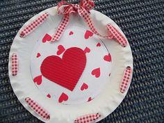 Srdiečkový tanierik - pre mamičku či babičku.  Tanier z papiera predierkujeme dierkovačom v rovnakých vzdialenostiach,prevlečieme stužku cez dierky a uviažeme na mašličku, zo vzorovaného srdiečkového papiera vystrihneme kruh a nalepíme ho do stredu tanierika, z vlnitého červeného papiera vystrihneme srdiečko a nalepíme,môžeme dolepiť aj fotku a použiť ako rámik.