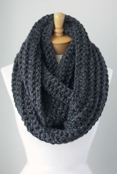 Grey knit infinity scarf. Useful for; keeping warm and layering with plain shirts.