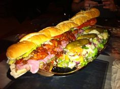 """21"""" panini loaded with corned beef, bacon, sausage, meatballs, spicy eggplant, three cheeses, lettuce, hot sauce, tomatoes & 1 pound of potato salad."""