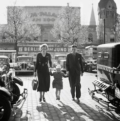 A German family walks between taxicabs in front of the Ufa-Palast movie theatre in Berlin, late 1920s or early 1930s