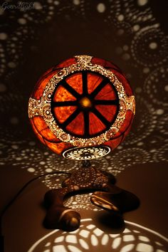 https://flic.kr/p/jDkRNh | Table lamp IX | Head of the lamp is made of Senegalese calabash. White parts are carved layer of the fruit which change the color to red/orange when the lamp is switched on. On the bottom of the lamp there's perforated closing part locked by magnets. The lamp was painted with wood oil and alcohol ink. Black parts are burnt calabash surface. The center element is genuine Baltic amber- ranked as the world's finest;  resin from the ancient trees dating back ~40…