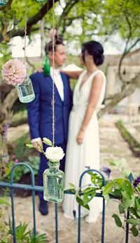 Secret Garden Wedding Decorations  - hanging bottles form trees with single stem flowers make a lovely backdrop