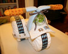 how to make this tricycle out of diapers, receiving blankets, socks, bib, ribbon, and a bottle.