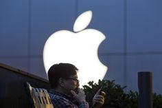 A man peers at a phone near an Apple store in Beijing in May 2016....